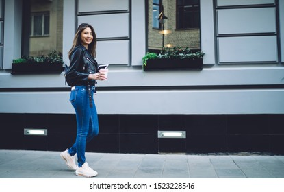 Side view of optimistic and positive ethnic woman in trendy outfit walking along street and drinking coffee while looking at camera