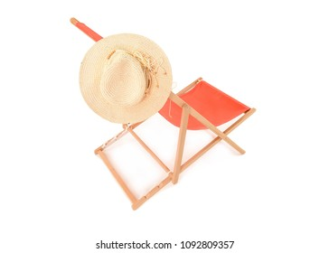 Side view of Orange Deckchair against a white background with cream colored sun hat hanging on it. Space for text.