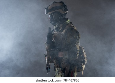 Side view orderly soldier wearing army ammunition while standing in smoke. Pacificator concept