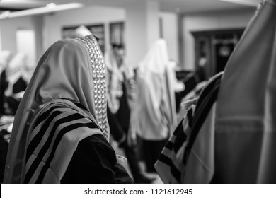 Side view of orthodox Jewish man covered in a prayer shawl praying in synagogue in black and white