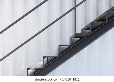 side view of outside metal staircase or fire exit stair with sheet corrugated wall background.