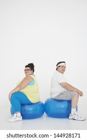 Side view of an overweight man and woman sitting on exercise balls