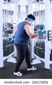 Side view of overweight person lose weight by weight lifting in the fitness center