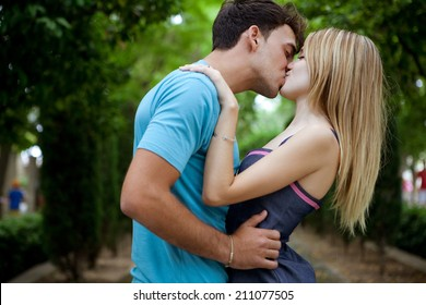 Side view of a passionate romantic young couple kissing and embracing while in a green park on holiday. Young people romantic lifestyle and love, outdoors.