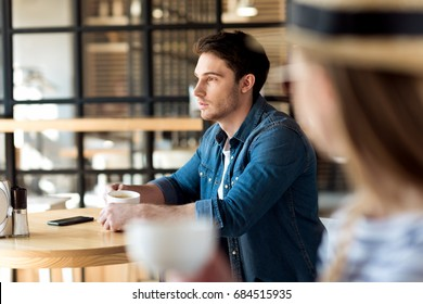 side view of pensive man with cup of coffee looking away while sitting at table in cafe
