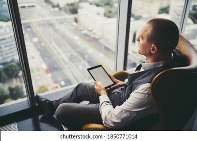 Side view of a pensive mature man entrepreneur in a plaid vest, sitting near the window on an orange armchair in an office cabinet on a top floor of a business high-rise with a digital tablet in hands