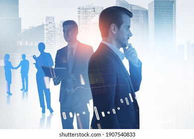 Side view of pensive young bearded European businessman standing in blurry city with his team and double exposure of graphs. Toned image
