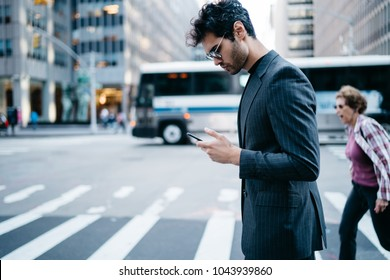 Side view of pensive young entrepreneur in stylish suit reading financial news in mobile application crossing zebra in downtown of metropolis.Confident proud CEO checking banking account on cellular