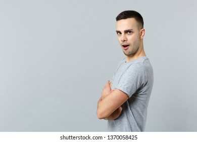 Side view of perplexed irritated young man in casual clothes looking camera, holding hands crossed isolated on grey background in studio. People sincere emotions lifestyle concept. Mock up copy space
