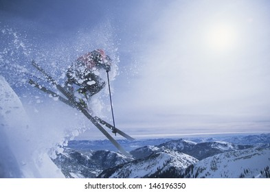 Side view of a person on skis jumping over slope