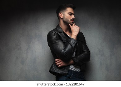 side view of a pesive man in leather jacket looking away from the camera