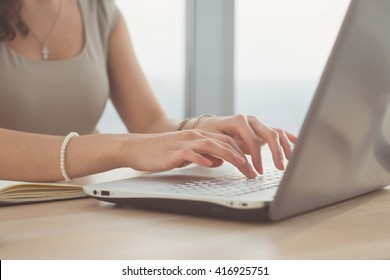 Side view photo of a female blogger, posting information in social network, using laptop, teleworking.