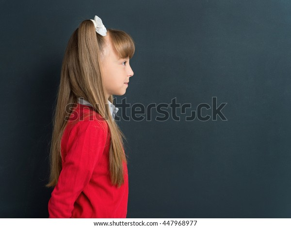 Side view photo of happy girl 10-11 year in front of a big chalkboard. Back to school concept.
