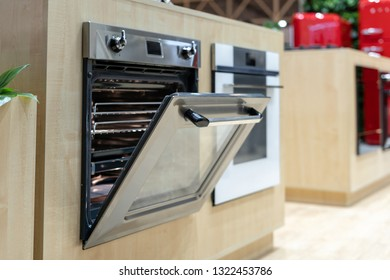 Side view photo of open door on new and modern built-in oven