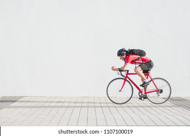 Side view photo of a Professional cyclist in red sportswear and a helmet riding a red bike on a white background. Porterter athlete cyclist on the background of a light wall. Copyspace