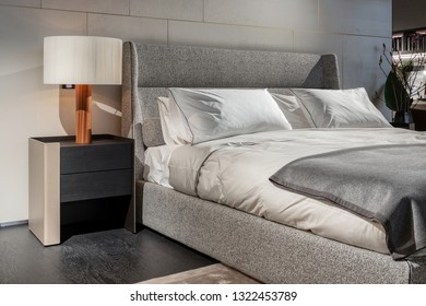 Side view photo of soft grey bed in bedroom interior with white lamp on the black wooden and metal bedside table