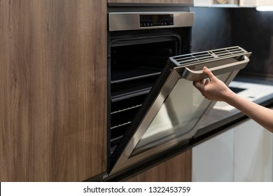 Side view photo of woman hand opening door on modern built-in oven in brown wooden kitchen cabinet