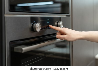 Side view photo of woman hand choose or switch program on electronic control panel for built-in oven in black kitchen cabinet