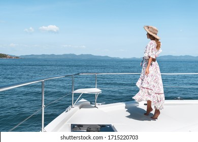 Side view photo of young amazing woman wearing  long dress and straw hat standing on the yacht. Copy space