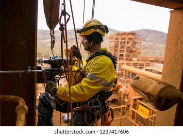 Side view picture of male industry rope access electrician abseiler wearing safety harness, helmet using two rope abseiling drilling metal structure with magnet construction mine site Perth Australia