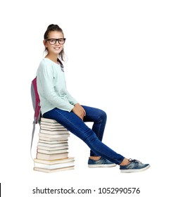 Side view picture of a  schoolgirl wearing casual clothes sitting on books