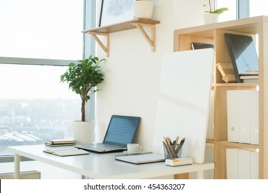 Side view picture of studio workplace with blank notebook, laptop. Designer comfortable work table, home office.