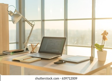 Side view picture of studio workplace with blank notebook, laptop. Comfortable work table, home office.