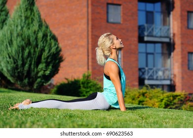 Side view picture of a woman practicing upward facing dog at the lawn in front of a multi storey building
