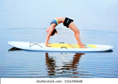 Side view picture of a yoga girl  in a bridge pose on a paddle board