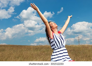 Side view picture of a young beautiful woman celebrating freedom while holding her hands up.