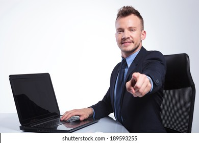 side view picture of a young business man sitting at his laptop and pointing at the camera with a smile on his face. on a gray studio backgroud