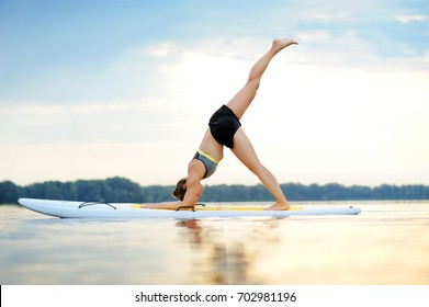 Side view picture of a young woman on paddle board practicing three legged down Dog yoga pose