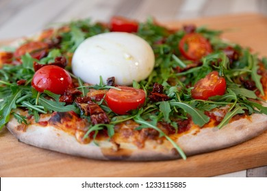 Side view of a pizza on a wooden board with cherry tomatoes, arugula, and burrata cheese on a wooden table and brick wall for background