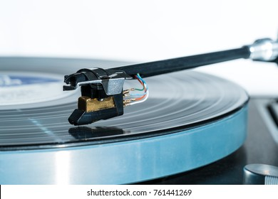 Side view of a playing vinyl record on vintage hi-fi stereo turntable with tonearm and cartridge in tracks of the LP