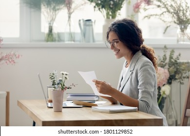 Side view pleasant smiling young businesswoman creative designer in eyeglasses reading paper letter correspondence with good news or banking notification, sitting at desk in modern showroom office.