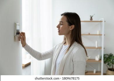 Side view pleasant young woman using smart home system or activating modern alarm system before leaving apartment. Happy lady turning off easy security technology, when returning house or flat.