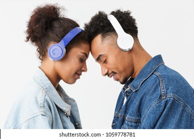 Side view of Pleased african couple in denim shirts touch each other's foreheads while listening music in headphones with closed eyes over grey background