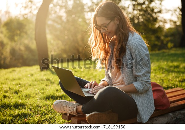 Side view of pleased brunette woman in eyeglasses sitting on bench in park and using laptop computer