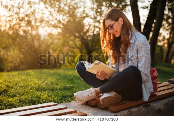 ベンチに座って公園で本を読む眼鏡をかけた、気に入ったブルネットの女性の側面