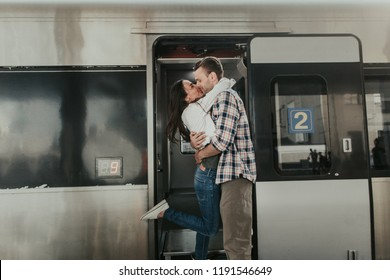 Side view pleased female embracing glad boyfriend while situating on platform during greeting