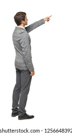 Side view of pointing business man. gesticulating young guy in suit. gesticulating young guy in suit.  Isolated over white background. A young guy in a gray suit shows something from the side.