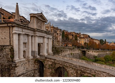 Side view of Porta San Giacomo and the walls of the upper city of Bergamo. Fortified and historical urban complex in Italy. Cityscape with cloudy sky.