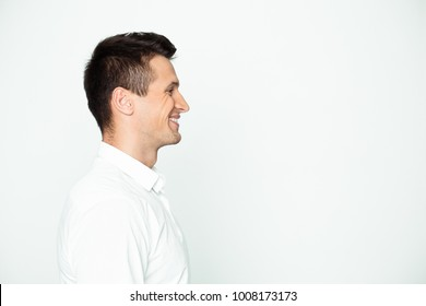 Side view portrair of smiling young handsome man in white shirt near copyspace.