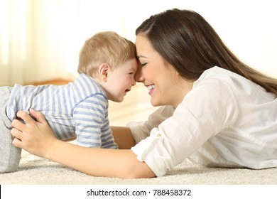 Side view portrait of an affectionate mother with joking her baby lying on a carpet at home
