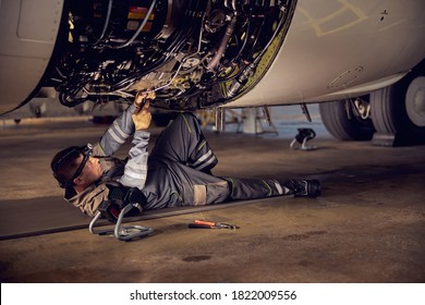Side view portrait of airplane maintenance mechanic inspecting on aircraft engine in aviation hangar