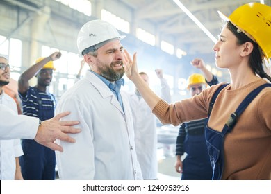 Side view  portrait of angry African-American worker fighting with managers during protest in industrial workshop, lens flare