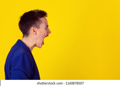 Side view portrait angry woman screaming, invisible sound coming out of open mouth, isolated on yellow background. Model in yellow shirt and blue suit. Negative human face expressions emotion reaction