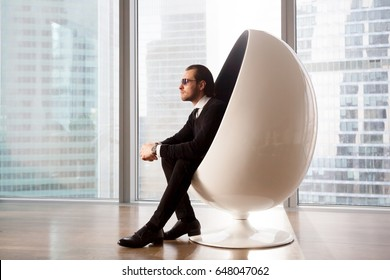Side view portrait of attractive man in business suit and sunglasses sitting in futuristic egg chair near window with urban scape outside. Successful businessman dreaming about future, enjoys luxury