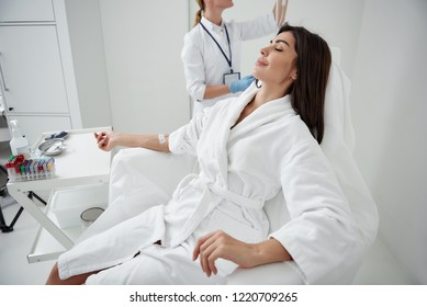 Side view portrait of attractive woman in white bathrobe sitting in armchair with closed eyes while receiving IV infusion
