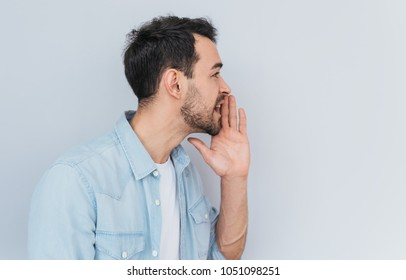 Side view portrait of attractive young Caucasian man sharing secret or whispering gossips, isolated over light grey background. Handsome male telling secret. Copy space for your advertising text.